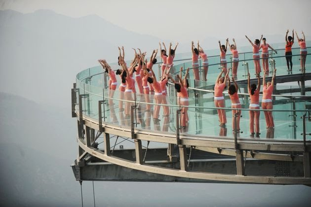 A large group of yoga enthusiasts practice yoga on a glass platform at Shilin Gorge in Beijing, China.