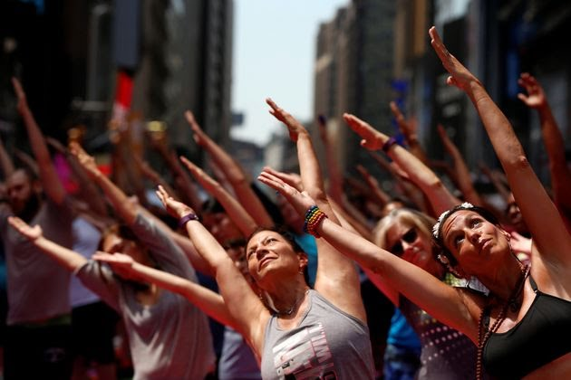 People participate in a yoga class during the 14th Annual Solstice in Times Square in New York.