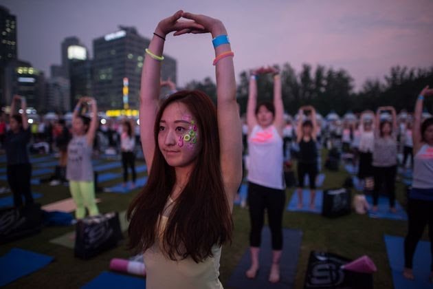 A yoga practitioner stretches during a mass event held as part of World Yoga Day in Seoul, South Korea.
